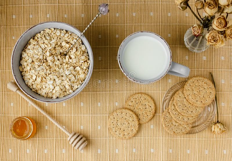 Healthy wholegrain breakfast: oatmeal, milk, biscuits, honey and vase with roses. Healthy breakfast: oatmeal cereal, cup of milk, jar of homemade jam, oatmeal royalty free stock photos