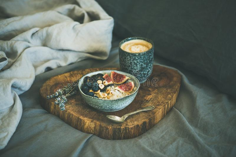 Rice coconut porridge with figs, berries and hazelnuts and coffee royalty free stock images