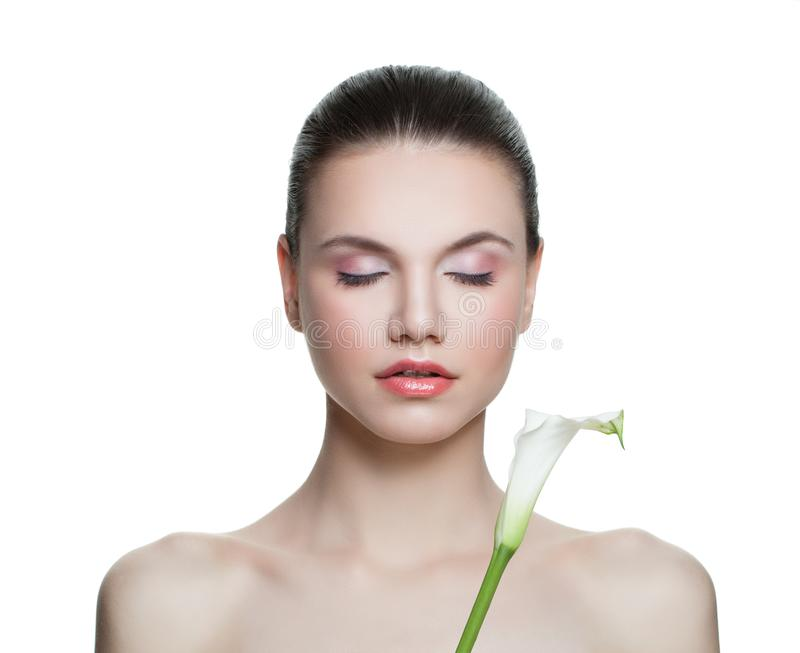 Healthy woman with clear skin and lily flower isolated on white. Spa beauty portrait royalty free stock photo