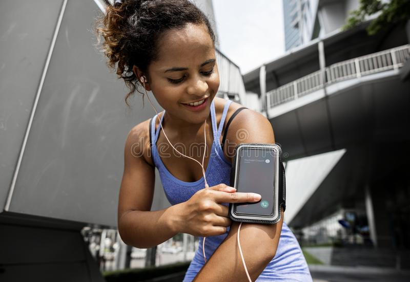 Healthy woman exercising using technology stock photography