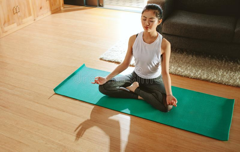 Healthy woman exercising yoga in living room. Healthy young woman exercising yoga in living room. Fitness female relaxing with yoga meditation at home stock image