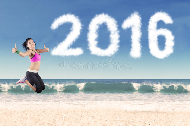 Healthy woman jumping with number 2016 at beach royalty free stock images