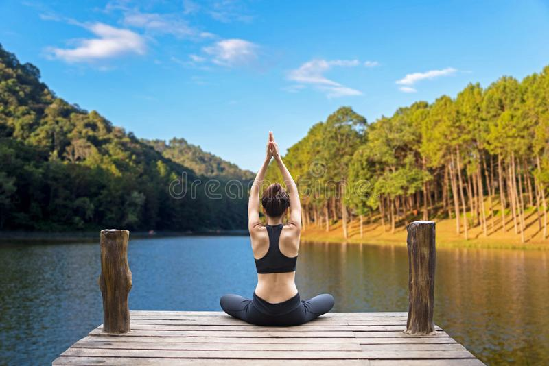 Healthy woman lifestyle balanced practicing meditate and zen energy yoga on the bridge in morning the nature. royalty free stock photography