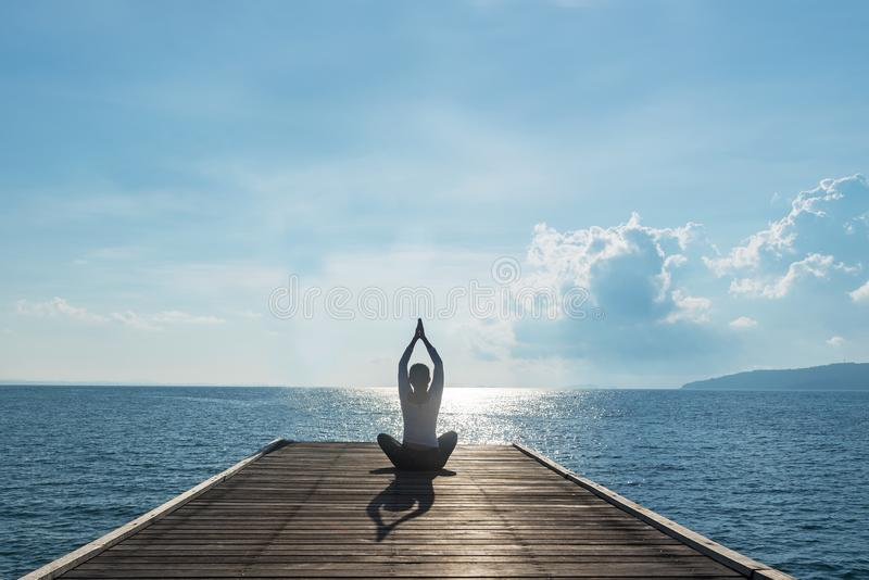 Healthy woman lifestyle balanced practicing meditate and zen energy yoga on outdoors the bridge in morning. Healthy life Concept royalty free stock image
