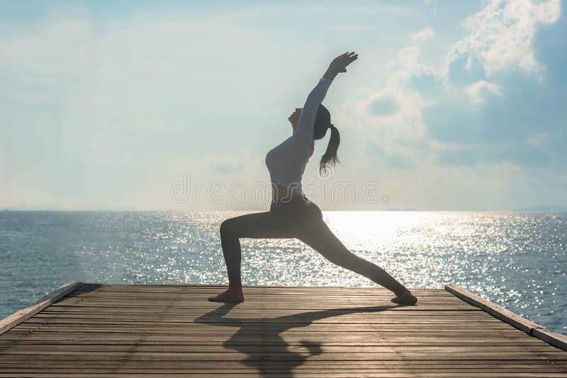 Healthy woman lifestyle balanced yoga ball practicing meditate and energy on the bridge in morning the seashore. Healthy Concept stock photo