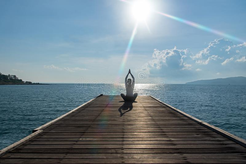 Healthy woman lifestyle exercising vital meditate and practicing yoga at on the bridge seashore, nature background. stock photo
