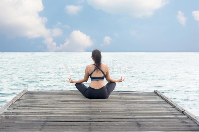 Healthy woman lifestyle meditate balanced yoga practicing and energy on the bridge. In morning the seashore. Healthy Concept stock photo