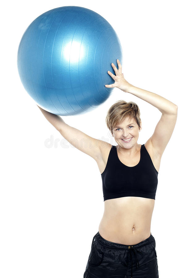 A healthy woman lifting big swiss ball stock images