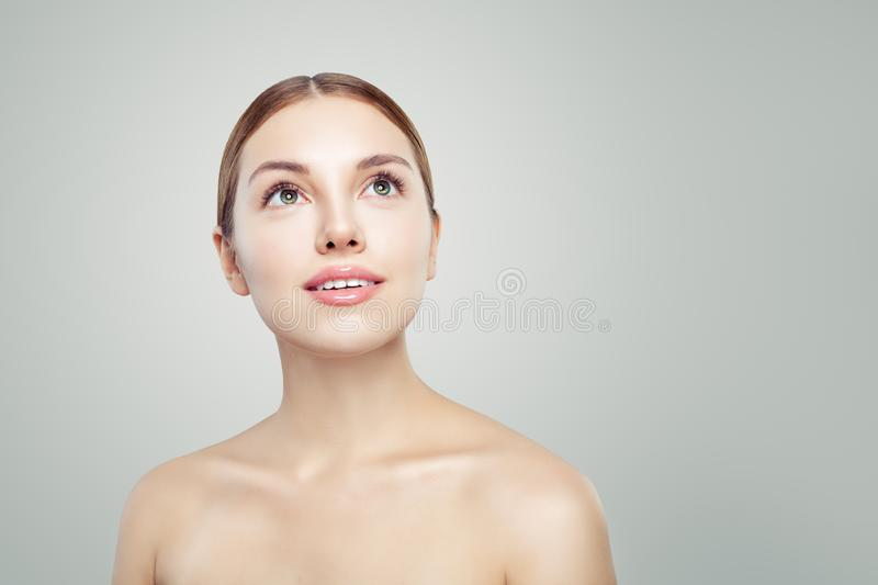 Healthy woman looking up. Young perfect model face with clear skin. Facial treatment, skincare and cosmetology concept royalty free stock photography