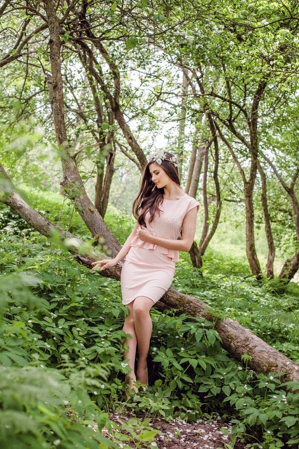 Healthy woman outdoors. Beauty girl female model brunette wearing flowers wreath in spring blossom garden royalty free stock image