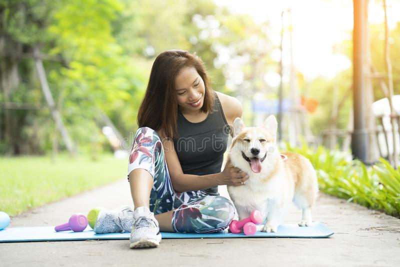 A healthy woman playing with a corgi puppy while exercising royalty free stock photography