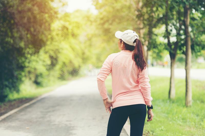 Healthy  woman relax after cool down and looking away in the road outdoor. Asian runner woman workout after fitness and jogging se royalty free stock photos