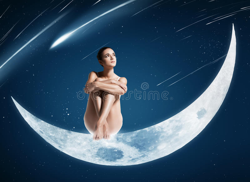 Healthy woman sitting on shiny moon stock photo