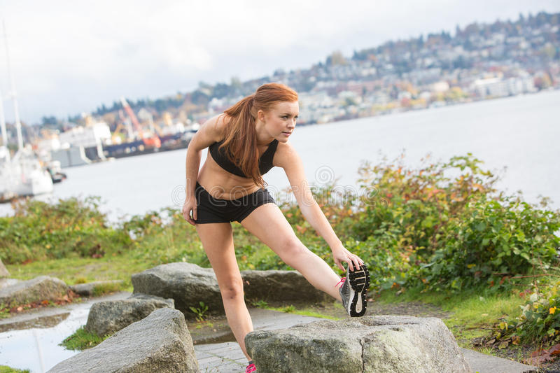 Healthy woman stretching before an outdoor run. Pretty woman with red hair stretching her legs before going on a run near the lake royalty free stock photography