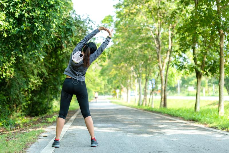 Healthy woman warming up stretching her arms. Asian runner woman workout before fitness and jogging stock photography