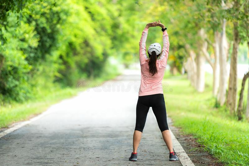 Healthy woman warming up stretching her arms. Asian runner woman workout before fitness and jogging session on the road nature par royalty free stock photography