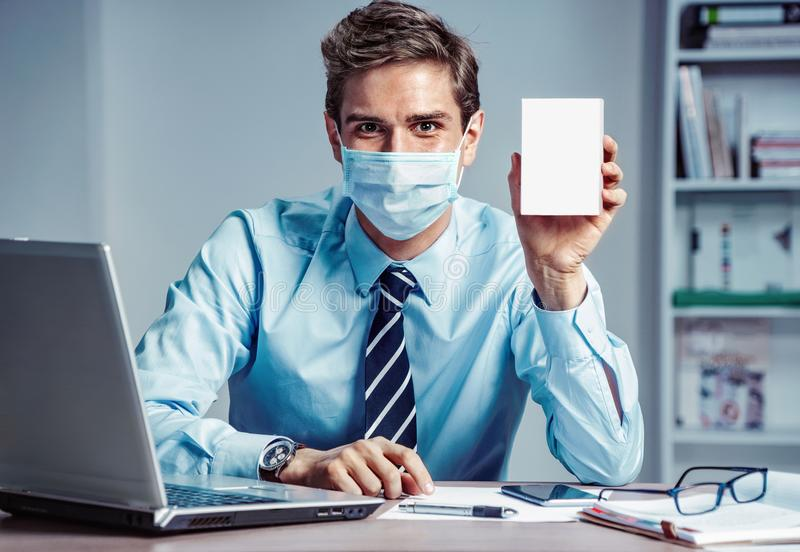 Healthy worker at the office holding white box of medicine. Photo of man wearing protective mask against infectious diseases and flu. Business and health care stock photos