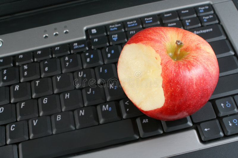 Healthy workplace. A business laptop with shiny bitten red apple depicting workplace wellness or a healthy school snack