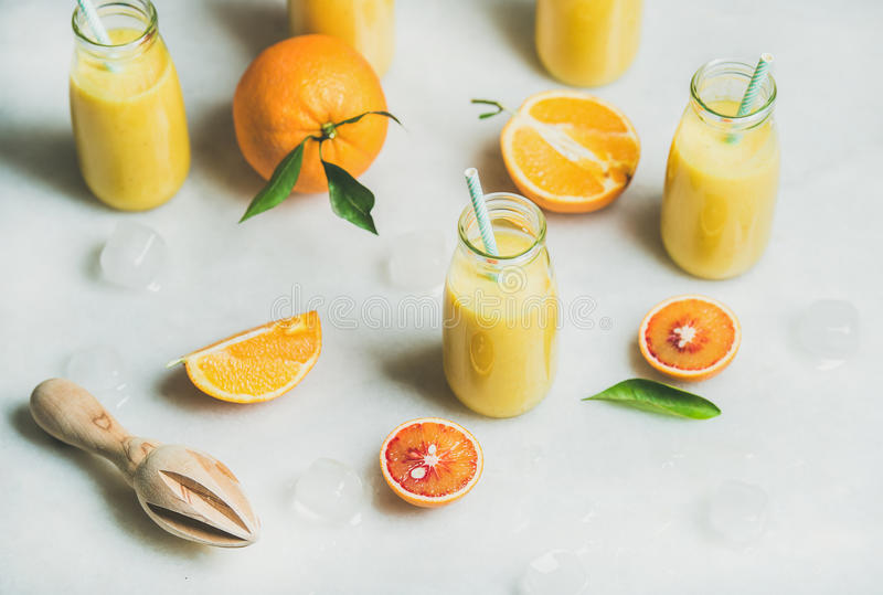 Healthy yellow smoothie with citrus fruit, marble background stock photo