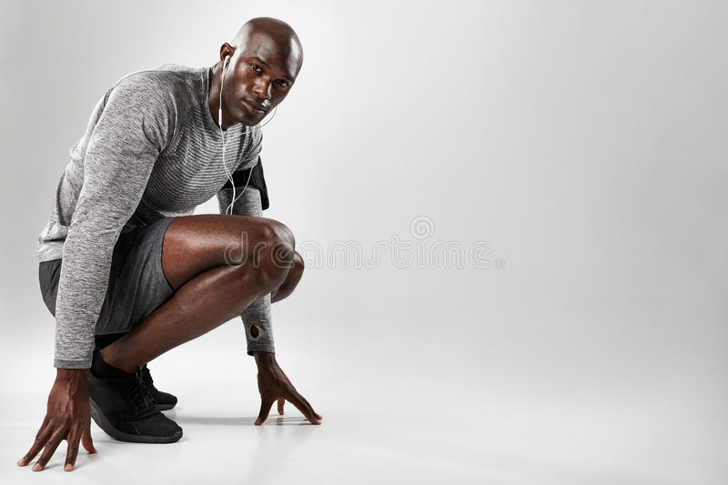 Healthy young black man kneeling on grey background stock photo