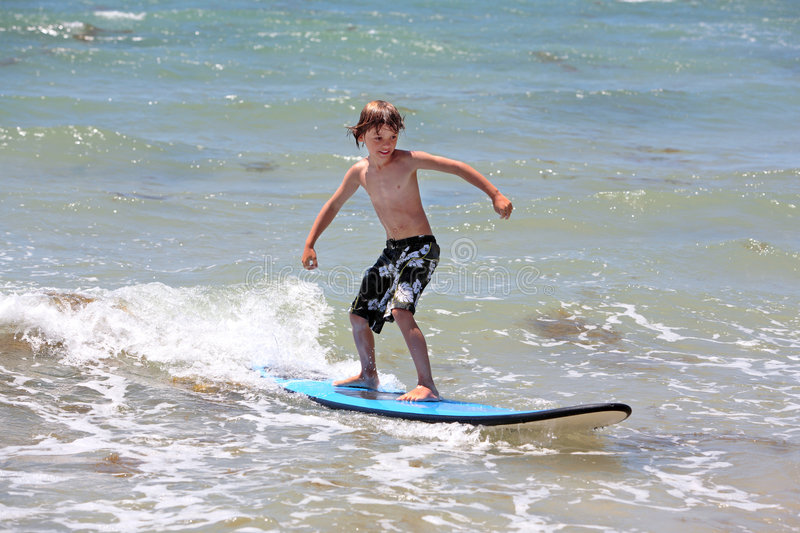 Healthy young boy learning to surf royalty free stock photography