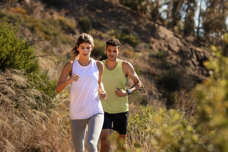 Healthy young couple running on mountain trail stock image
