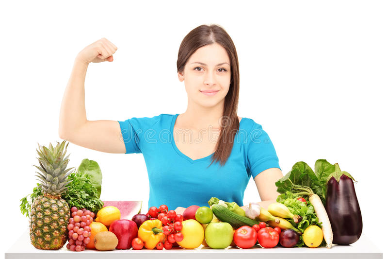 Healthy young female showing her muscle and sitting behind a pile of fruits and vegetables stock images