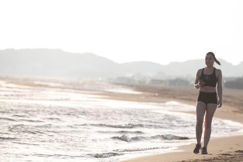 Healthy young fitness woman runner running on sunrise seaside tr royalty free stock photo