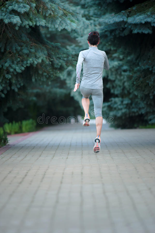 Healthy young fitness woman trail runner running at the park. Ba royalty free stock image