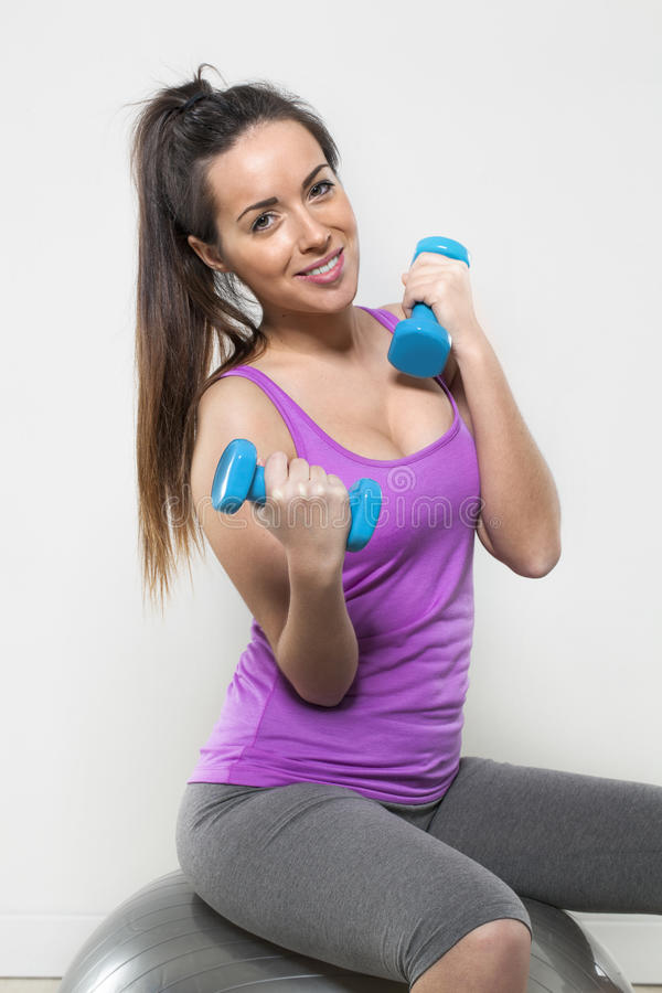 Healthy young lady with weights and fitness ball royalty free stock photography
