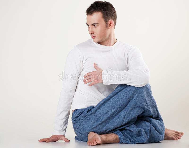 Healthy young man doing yoga. Spine twisting pose royalty free stock photo