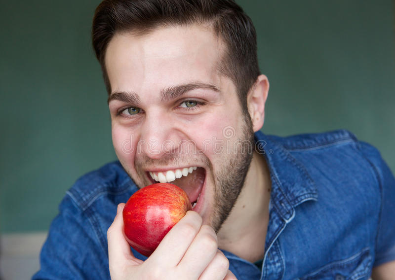 Healthy young man eating apple stock photos