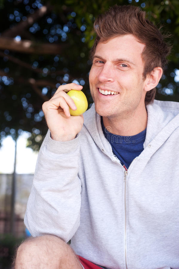 Healthy young man holding apple royalty free stock image