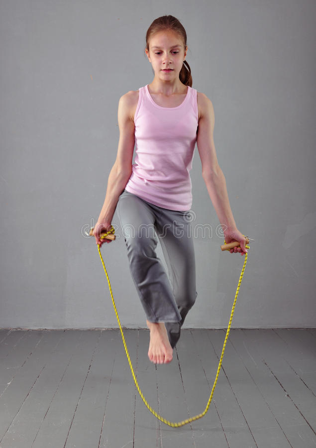 Healthy young muscular teenage girl skipping rope in studio. Child exercising with jumping on grey background. stock photography