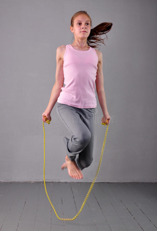 Healthy young muscular teenage girl skipping rope in studio. Child exercising with jumping on grey background. royalty free stock image