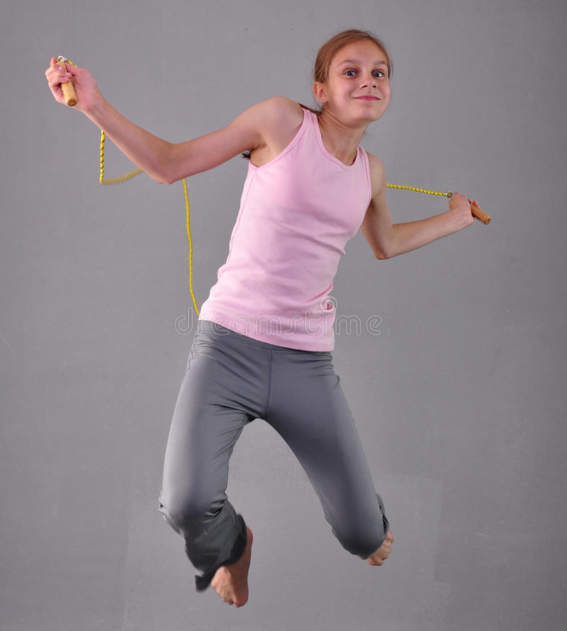 Healthy young muscular teenage girl skipping rope in studio. Child exercising with jumping high on grey background. royalty free stock photo