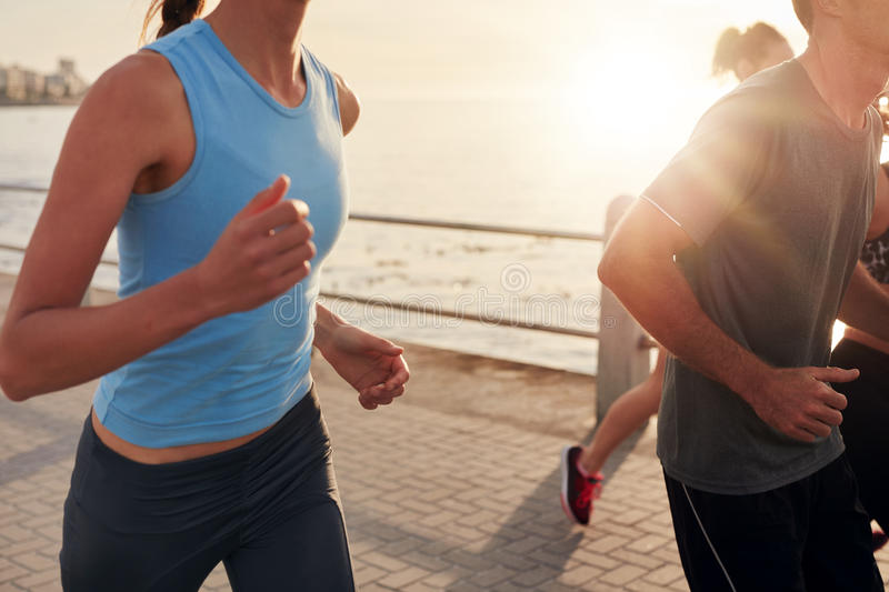 Healthy young people running together in city stock photos