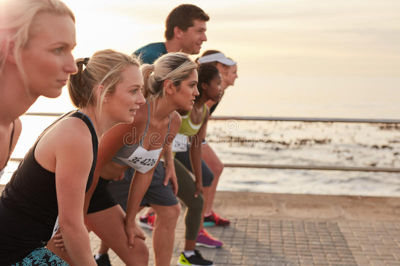 Healthy young people running together in city stock photography