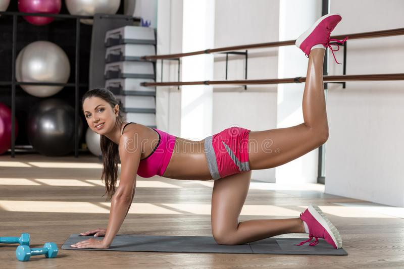 Healthy young sportswoman doing the exercises on all fours arching back straightening leg up. stock images