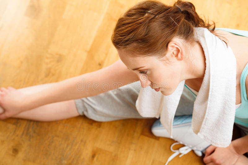 Healthy young sportswoman stretching at gym. Exercising royalty free stock photography