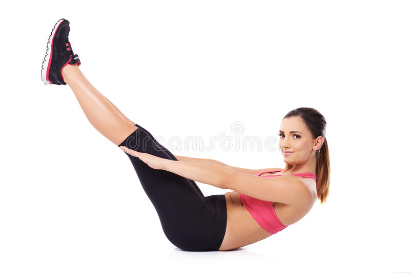 Healthy young woman doing sit ups. Healthy young woman smiling at the camera working out doing sit ups with her legs raised in the air royalty free stock photography