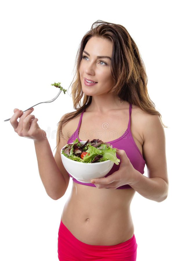 Healthy young woman eating green salad stock images