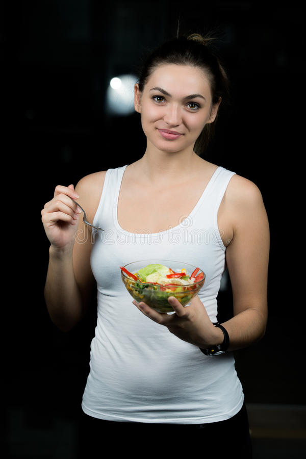 Healthy young woman eating vegetables green salad at dark gym royalty free stock photography