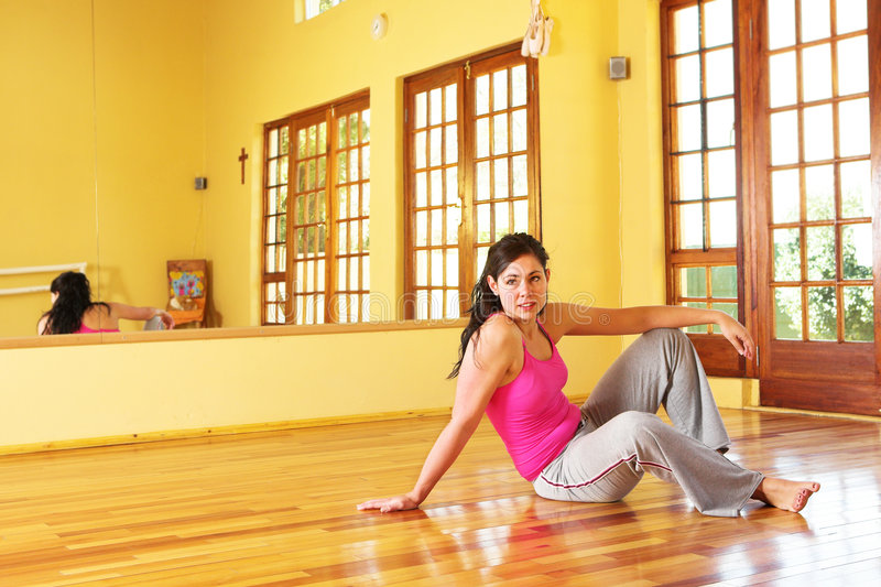 Healthy young woman in gym outfit sitting on the floor stock photo
