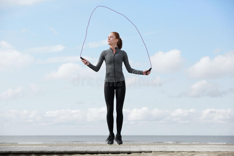 Healthy young woman with jump rope royalty free stock photo