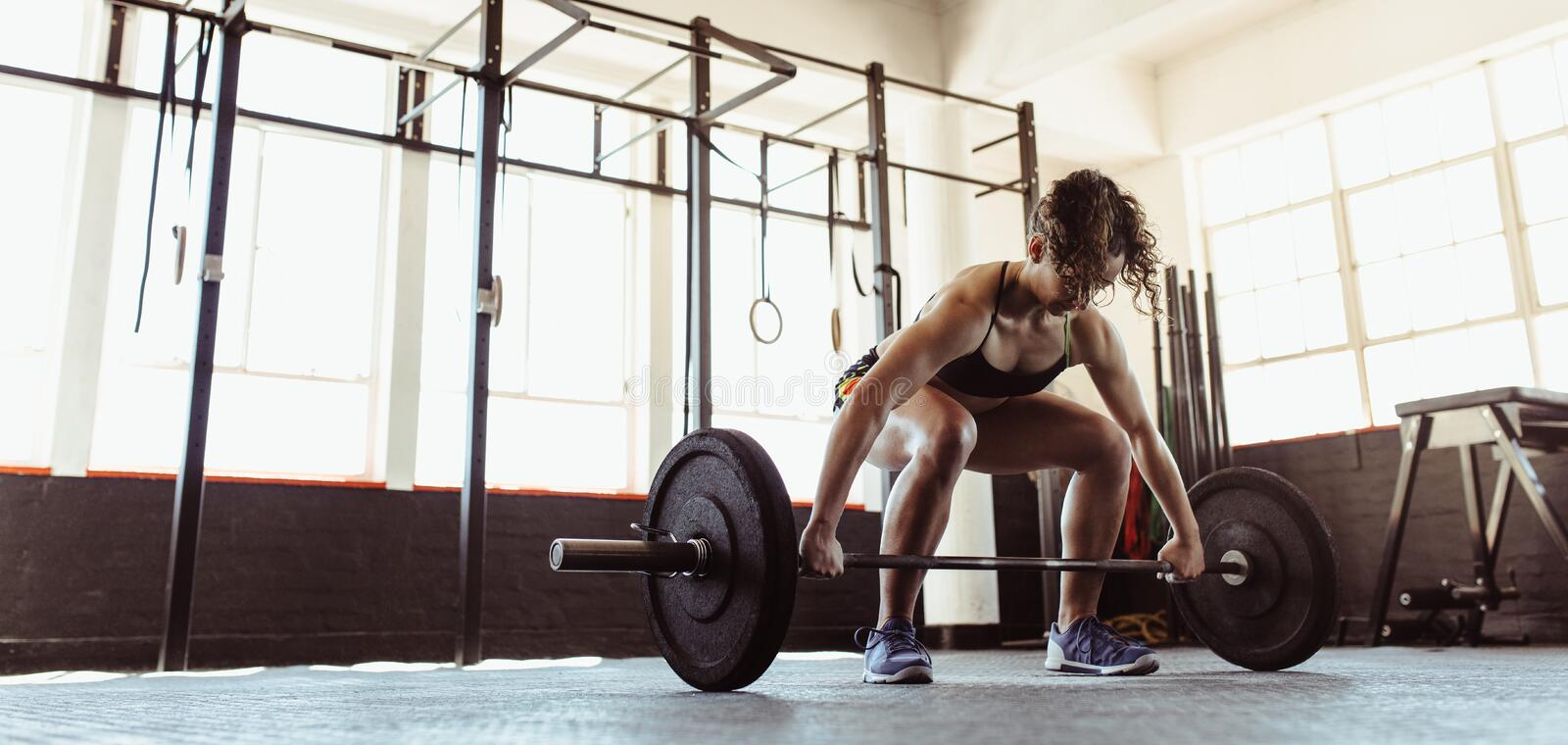 Healthy young woman lifting a barbell stock image