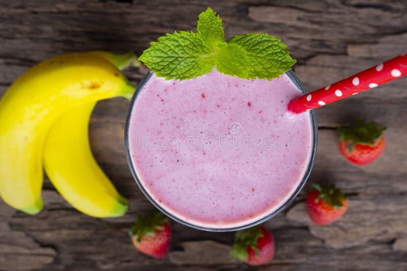 Healthyon för dryck för blandning för milkshake för fruktsaft för frukt för jordgubbe- och banansmoothie färgrik som en träbakgru royaltyfri bild