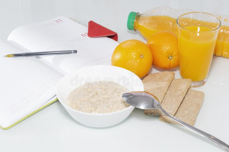 Healty breakfast with muesli, and orange juice. View from above on wooden table with notepad for copy space. stock photos