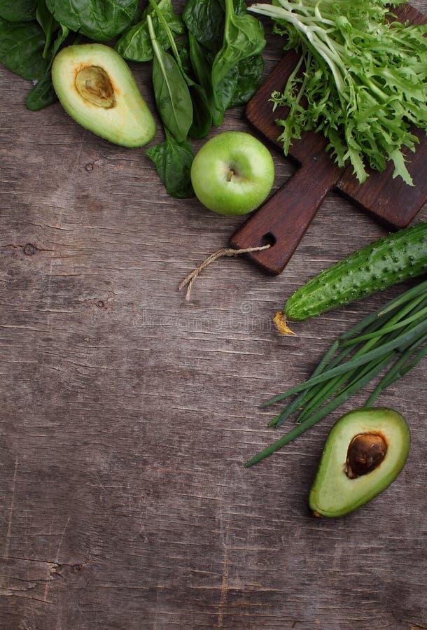 Healty zieleni warzywo: szpinak, ogórek, sałata, jabłko i avocado na ciemnym tle, zdjęcie stock