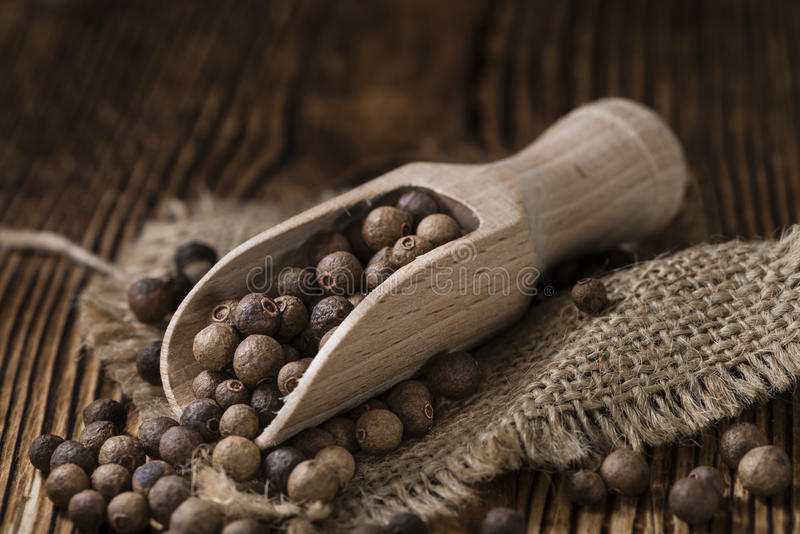 Heap of Allspice (selective focus). Heap of dried Allspice (selective focus) on an old wooden table royalty free stock photo
